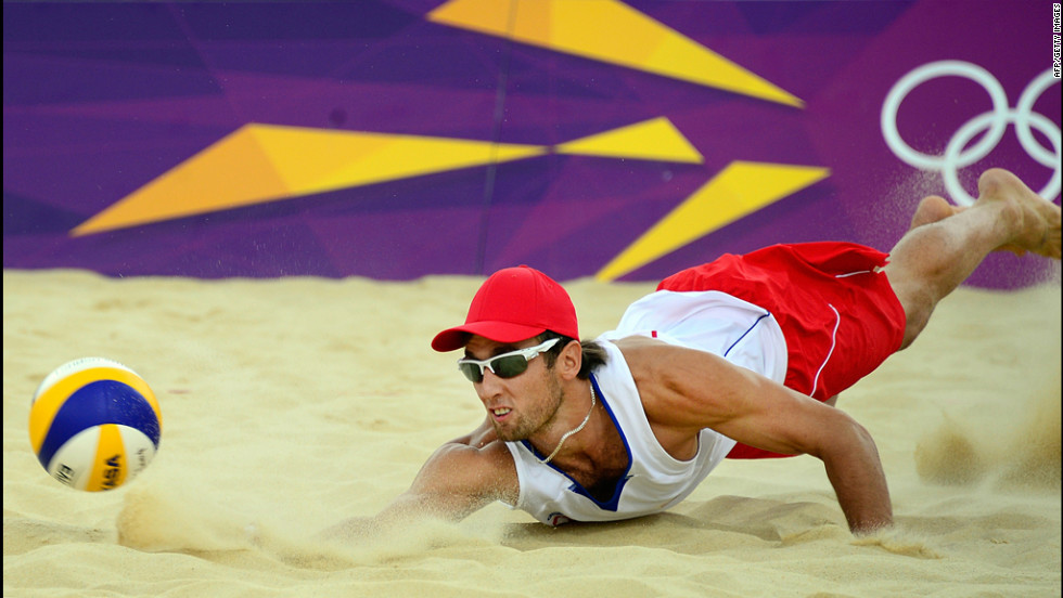 Poland's Grzegorz Fijalek dives for the ball during a beach volleyball match.