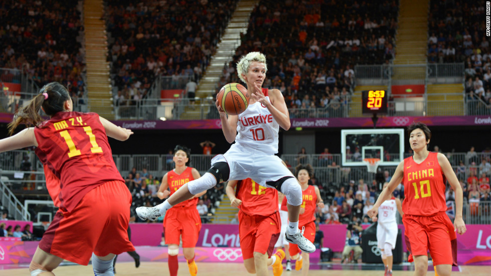Turkish guard Isil Alben, center, jumps with the ball during the women's preliminary round basketball match between Turkey and China on Friday.