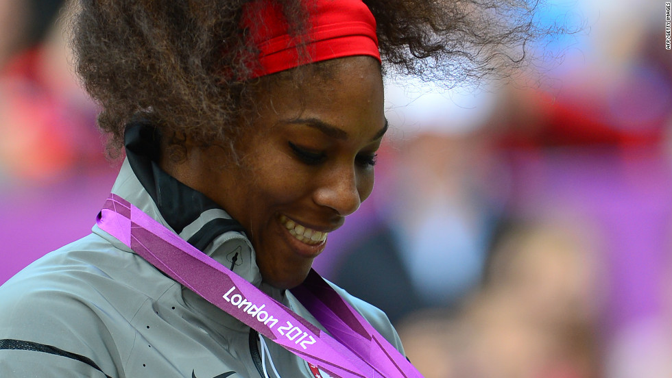 Williams admires her gold medal during the medal ceremony after defeating Sharapova in the women's singles match.