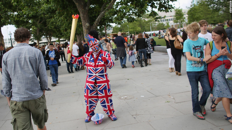 A performer dressed in a Union Flag suit and holding a mock Olympic flame entertains crowds on the South Bank in London.