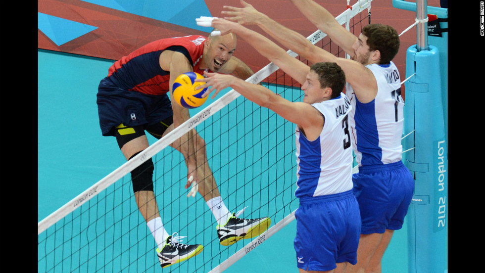 William Priddy, left, spikes as Russia's Nikolay Apalikov, center, and Maxim Mikhaylov, right, attempt to block during a men's preliminary pool B volleyball match.