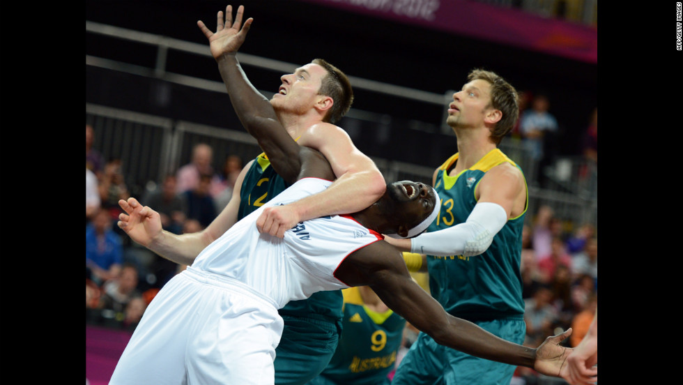 Australian center Aron Baynes, left, British forward Pops Mensah-Bonsu, center, and Australian forward David Andersen, right, vie during a men's preliminary round group B basketball match.