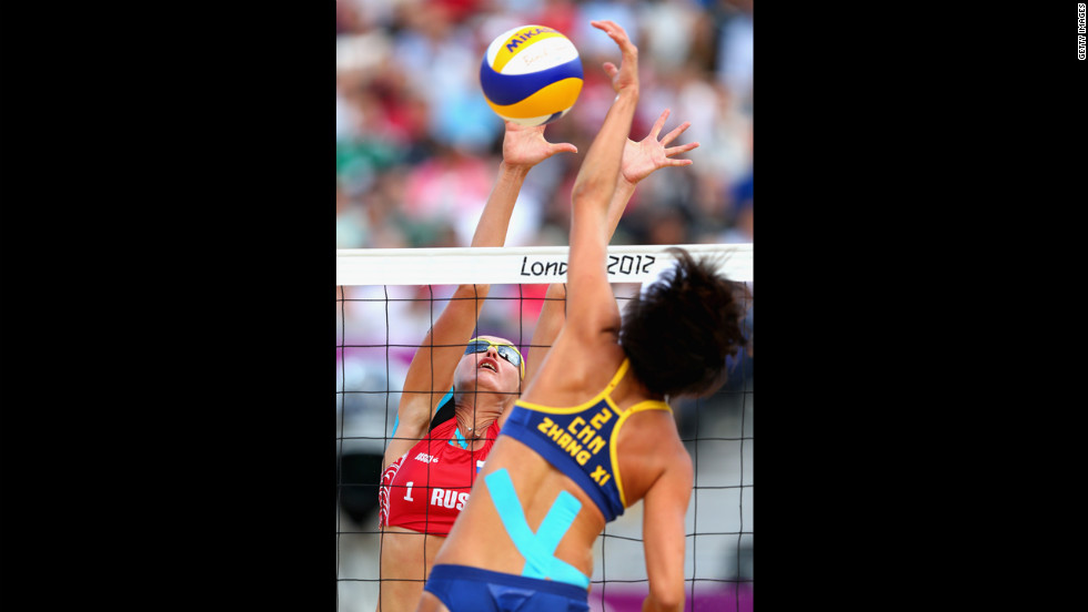 Xi Zhang of China blocks Ekaterina Khomyakova of Russia during a women's beach volleyball match.