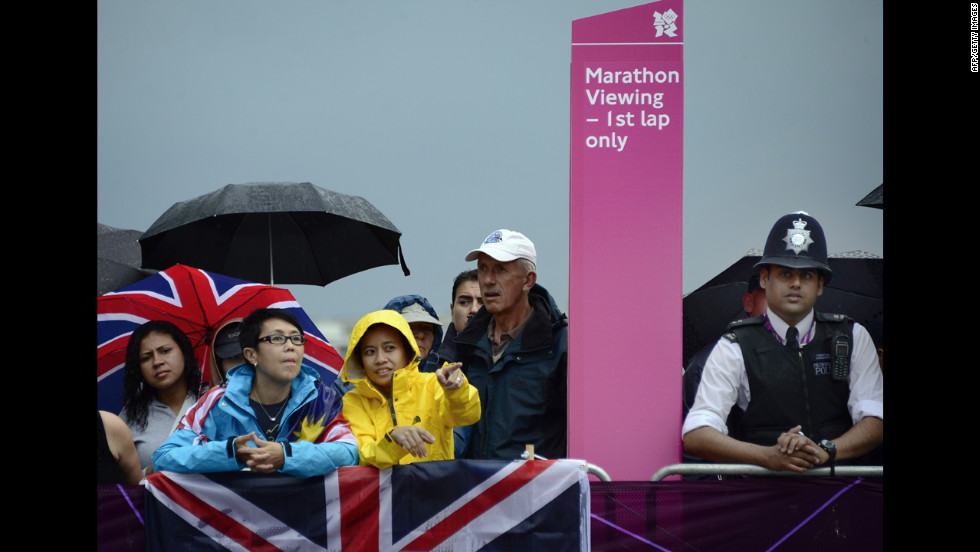 Spectators view the course as rain falls during the women's marathon race.