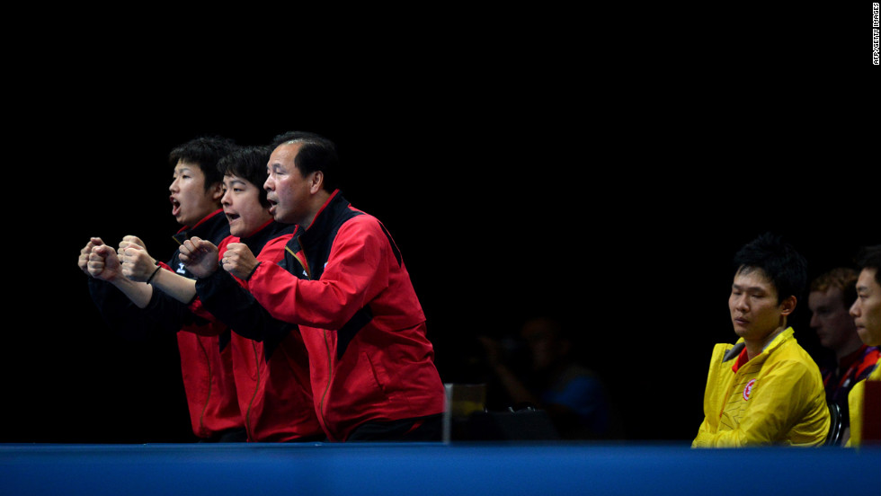 Japan's table tennis team celebrates a point for Koki Niwa against Hong Kong's Peng Tang during a men's quarterfinal match.