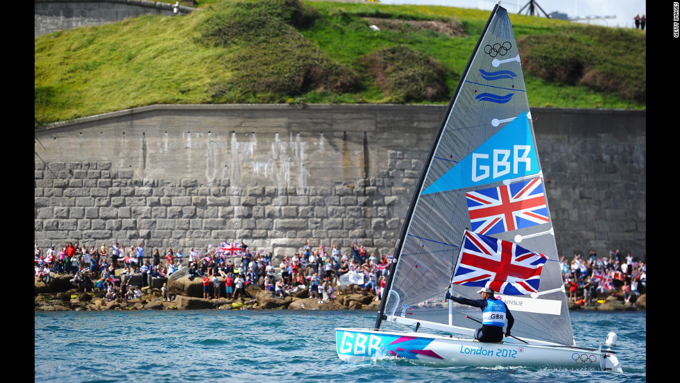 Ben Ainslie of Great Britain hoists the Union Jack and acknowledges the cheers from fans after winning the gold medal in the finn class medal race in Weymouth, England.