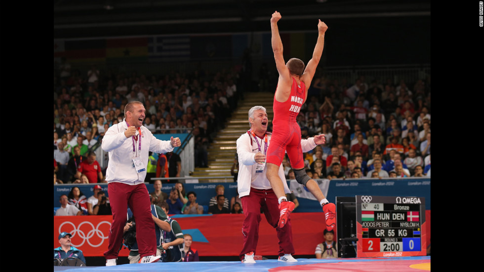 Peter Modos of Hungary jumps for joy after winning the men's Greco-Roman 55-kilogram wrestling bronze medal bout against Haakan Erik Nyblom of Denmark.