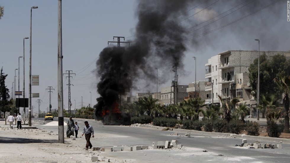 A vehicle burns as Syrians walk through debris from clashes between Syrian armed forces and rebels in the northern city of Aleppo on Saturday, August 4.