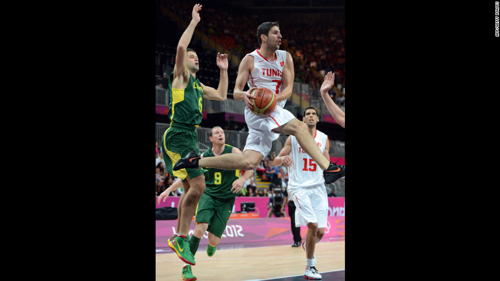 Tunisian guard Mourad El Mabrouk, center, leaps with the ball during the men's basketball preliminary round match against Lithuania.