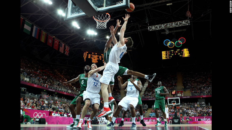 Fabien Causeur of France, center, drives for a shot attempt against Nigeria during the men's basketball preliminary round match.
