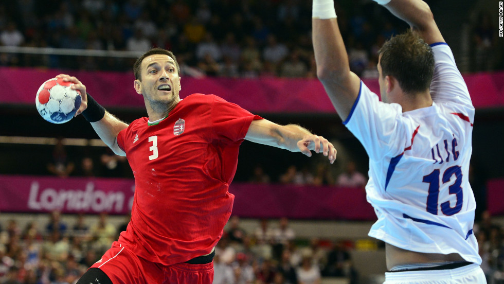 Hungarian back Ferenc Ilyes, left, takes a shot in front of Serbia's Momir Ilic during the men's preliminary Group B handball match.