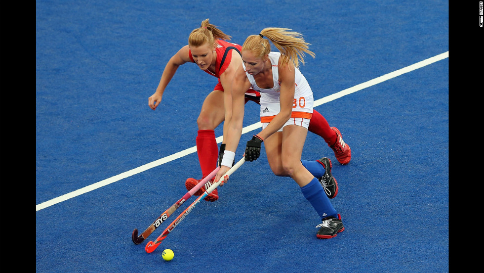 Nicola White, in red,  of Great Britain and Margot van Geffen of the Netherlands contest for the ball during  women's hockey play.