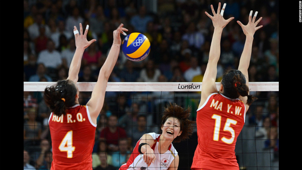 Japan's Saori Kimura, center, spikes as China's Hui Ruoqi and Ma Yunwen attempt to block during the women's quarterfinal volleyball match.
