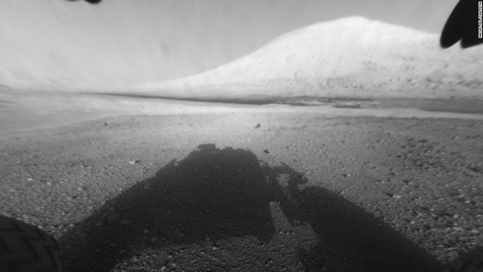 "This image shows Curiosity's main science target, ""Mount Sharp."" The rover's shadow can be seen in the foreground. The dark bands in the distances are dunes."