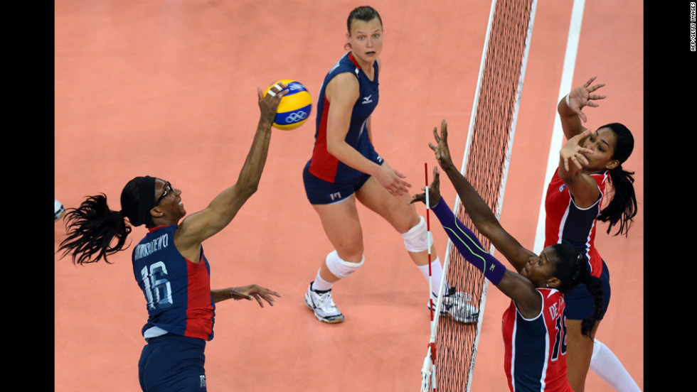 Foluke Akinradewo, left, of the United States spikes during the women's quarterfinal volleyball match between the USA and the Dominican Republic.
