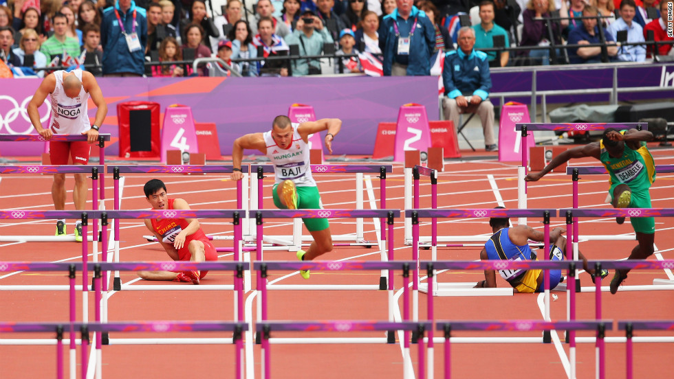 Balazs Baji, center, of Hungary leads the pack as Xiang Liu of China falls over a hurdle in the men's 110-meter hurdles round 1 heats.