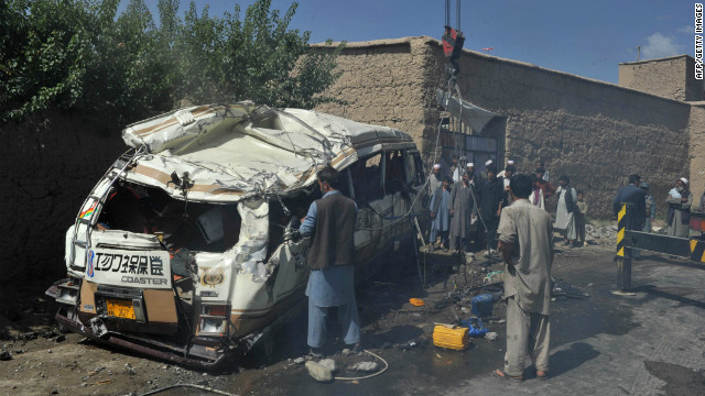 Afghan policemen and villagers at the scene where a civilian minibus was hit by a remote-controlled bomb in Paghman district of Kabul on August 7, 2012.