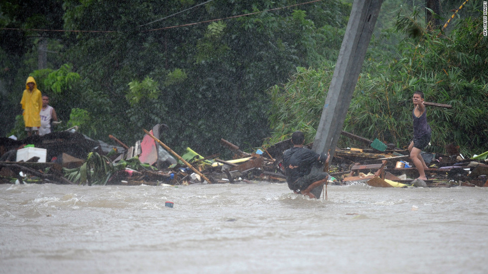 A man clutches a pole in floodwaters after a river overflowed following torrential rain in Manila.