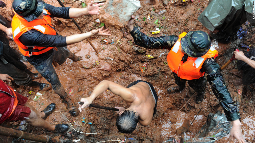 Rescuers dig through the rubble of a landslide caused by flooding as they try to rescue victims in Quezon City in suburban Manila.