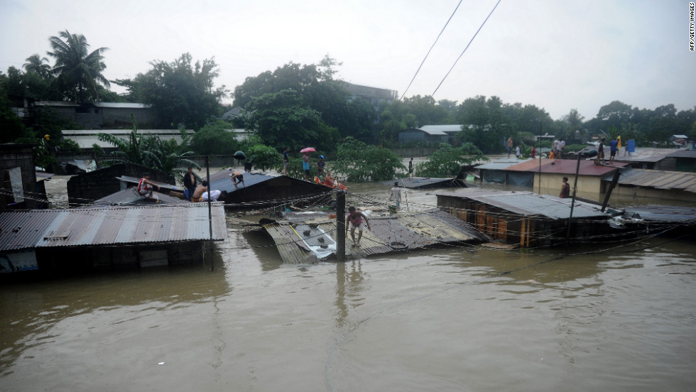 Residents seek shelter on the roofs of their homes as floodwaters continue to rise in Manila.