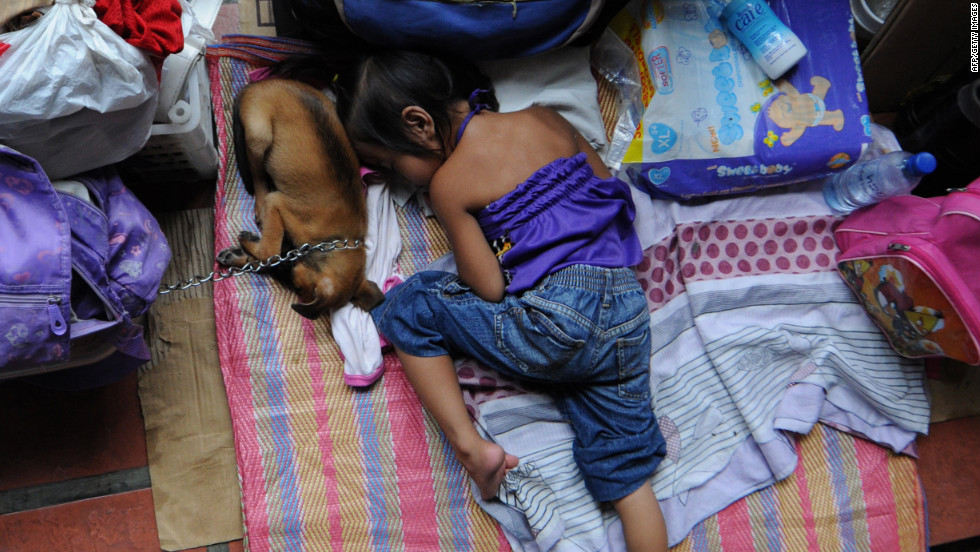 A child, one of the thousands of residents affected by the severe floodings, sleeps next to the family's dog at a temporary evacuation center.