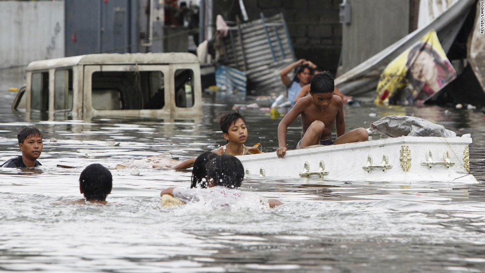 Residents use a coffin as a boat in floodwaters in Quezon city, Metro Manila.