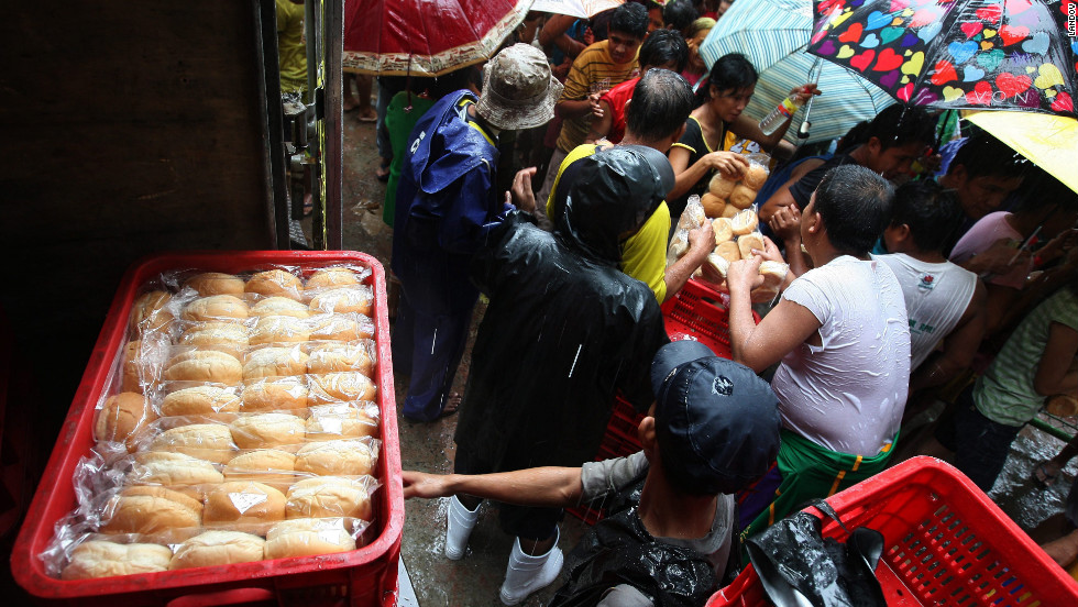 Filipino flood evacuees crowd around a truck giving out donated bread at an evacuation center in Marikina City, east of Manila.