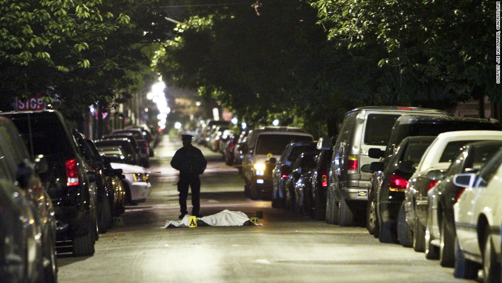 A police officer stands near a body after an argument erupted in a fatal stabbing last April in South Philadelphia.