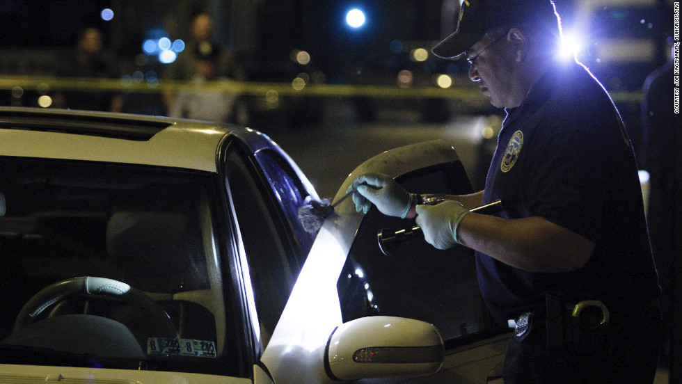 A member of a police crime scene unit gathers evidence from a homicide in May in North Philadelphia.