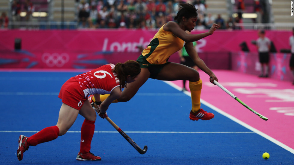 Japan's Murakami Ai, left, and Sulette Damons of South Africa vie for the ball during the women's field hockey classification match.