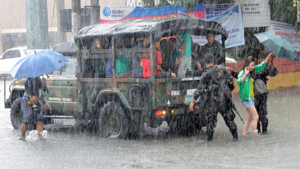 Philippines army soldiers assist people during heavy rains north of Manila on Wednesday, August 8.