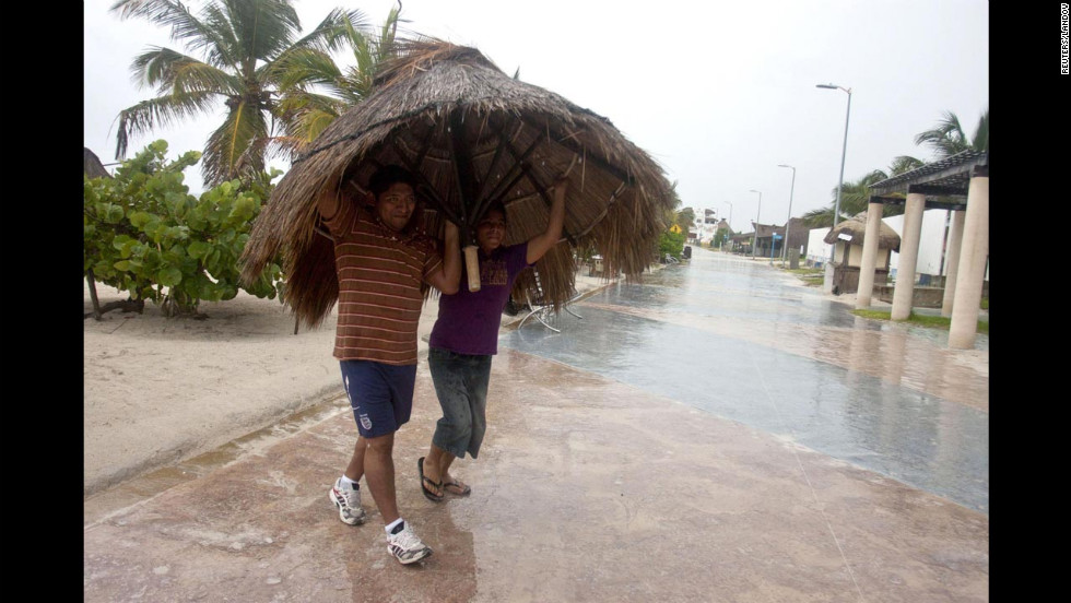 Residents get creative to take shelter from the rain near the beach of Mahahual.