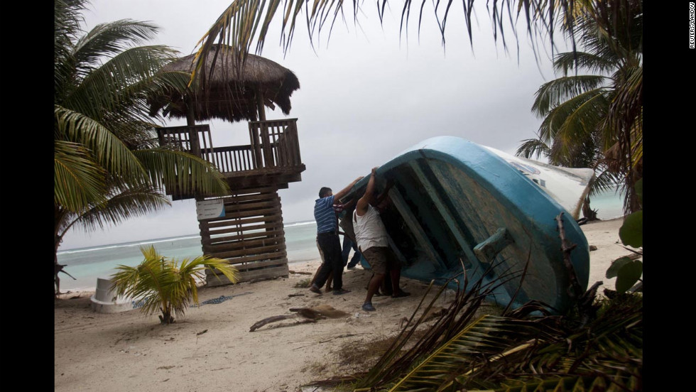 Residents move a boat that was dislodged by the storm in Mahahual.