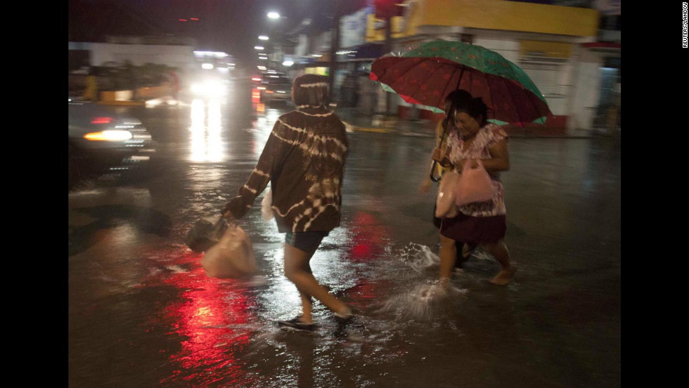 Residents of Felipe Carrillo Puerto, Mexico, cross a street flooded by the rains from Hurricane Ernesto.