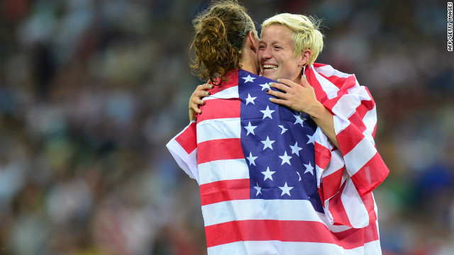United States's midfielder Megan Rapinoe (R) and United States's forward Lauren Cheney celebrate with their national flag during the final of the women's football competition of the London 2012 Olympic Games USA vs Japan on August 9, 2012 at Wembley stadium in London. The US team defeatd Japan 2-1. AFP PHOTO / LUIS ACOSTA (Photo credit should read LUIS ACOSTA/AFP/GettyImages)