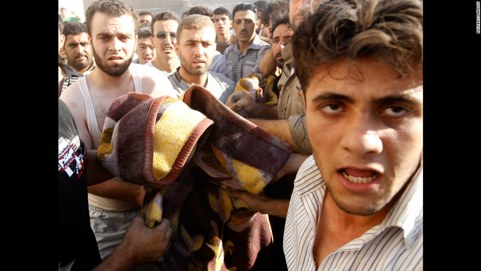 Men carry the body of a boy killed in an airstrike in the village of Tel Rafat.