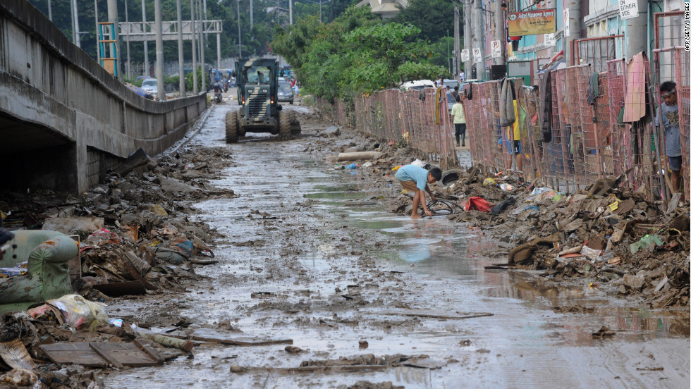 Philippine army corp engineers clear mud and debris from a street in a Manila suburb on Friday, August 10, after days of heavy rain and flooding.