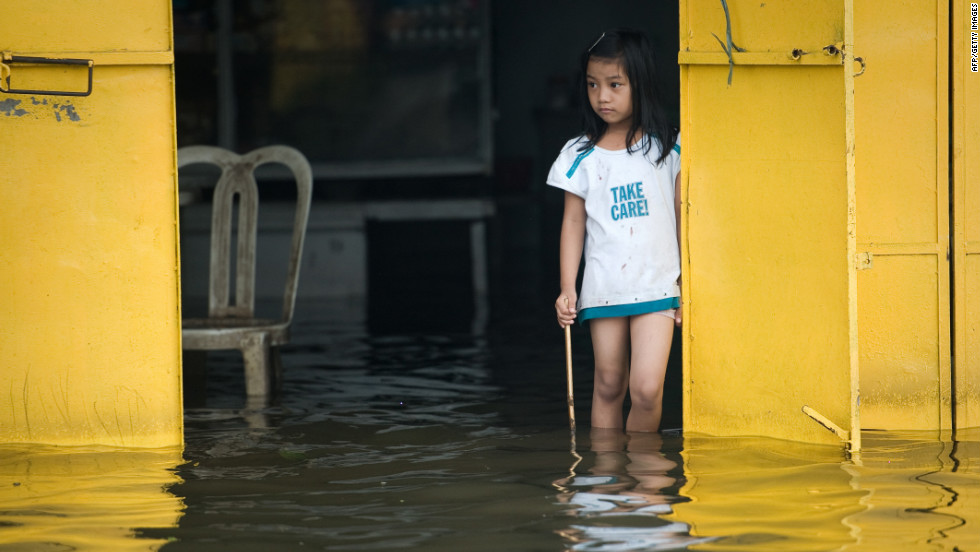 A girl eyes floodwaters Friday from a restaurant in Apalit outside Manila.
