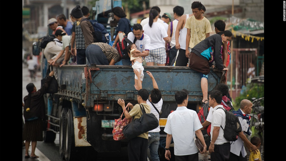 Filipinos step down from a truck Friday after crossing through floodwaters in Apalit outside Manila.