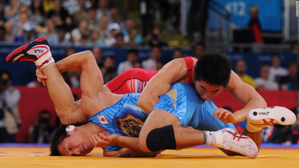 South Korea's Jincheol Kim, right, and Kenichi Yumoto of Japan compete in the men's freestyle 55-kilogram wrestling.