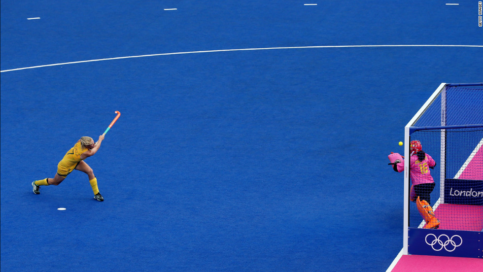 Australia's Jodie Schulz, left, shoots a penalty shot against Chinese goalkeeper Yimeng Zhang during the women's field hockey classification match.