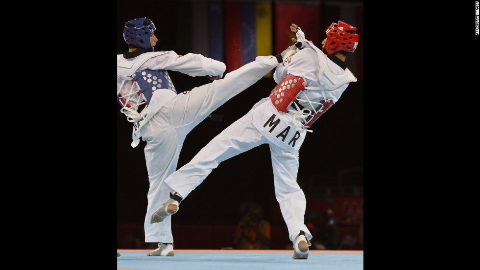 Afghanistan's Nesar Ahmad Bahawi, left, directs a kick against Morocco's Issam Chernoubi during the men's under 80-kilogram taekwondo bout.