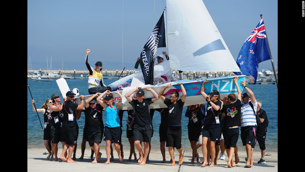 Jo Aleh, left, in the black cap, and Olivia Powrie, in the white cap, of New Zealand celebrate  winning the gold medal in the women's 470 sailing class.