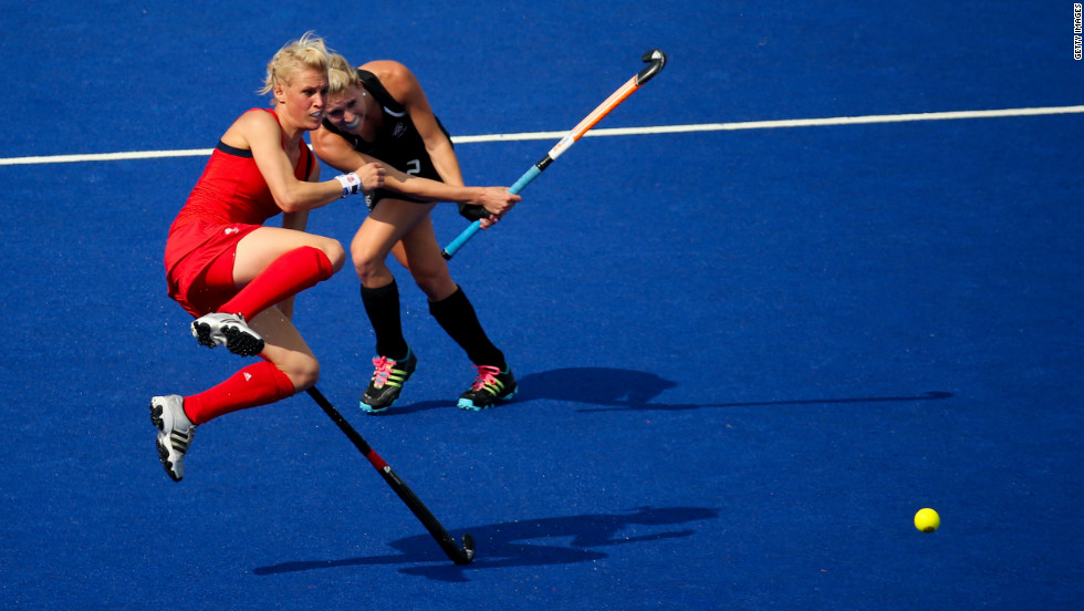 Great Britain's Alex Danson, left, jumps out of the way of New Zealand's Emily Naylor during the women's field hockey bronze medal match.