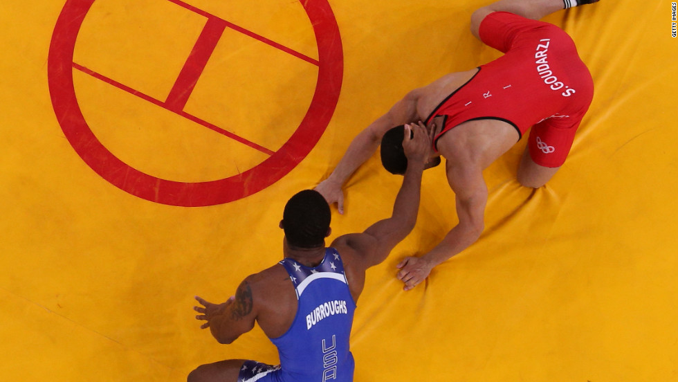 Jordan Ernest Burroughs of the United States, in blue, competes with Sadegh Saeed Goudarzi of Islamic Republic of Iran in the men's freestyle 74 kilogram wrestling.