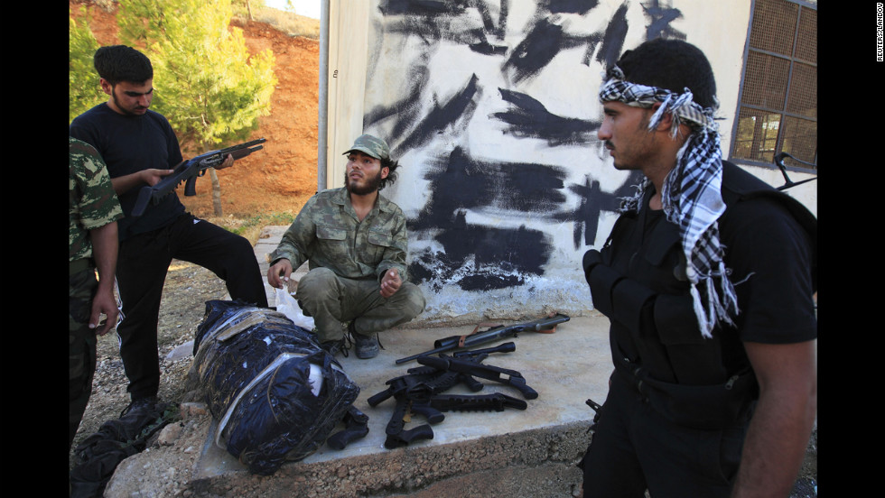 Free Syrian Army members check a confiscated cache of weapons found on a truck that was searched at a checkpoint in Dana.