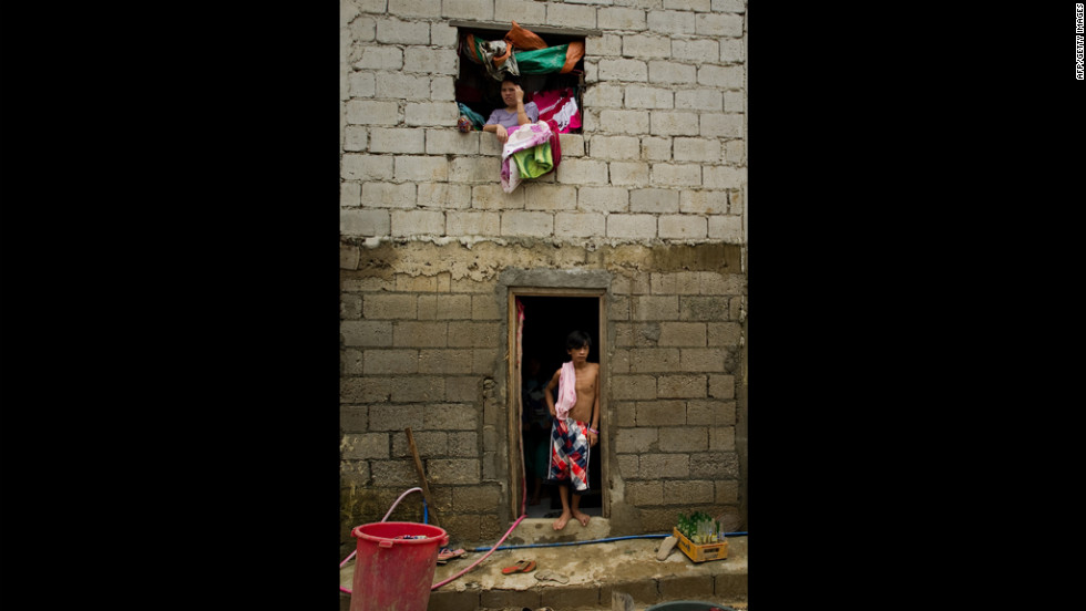 Residents of the Tomana slum in the Manila suburb of Marikina stand inside their home after water finally recedes.
