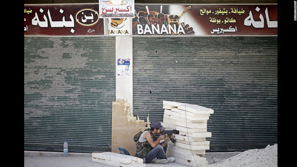 A Free Syrian Army fighter aims his rifle during heavy fighting in the Salaheddine neighborhood.