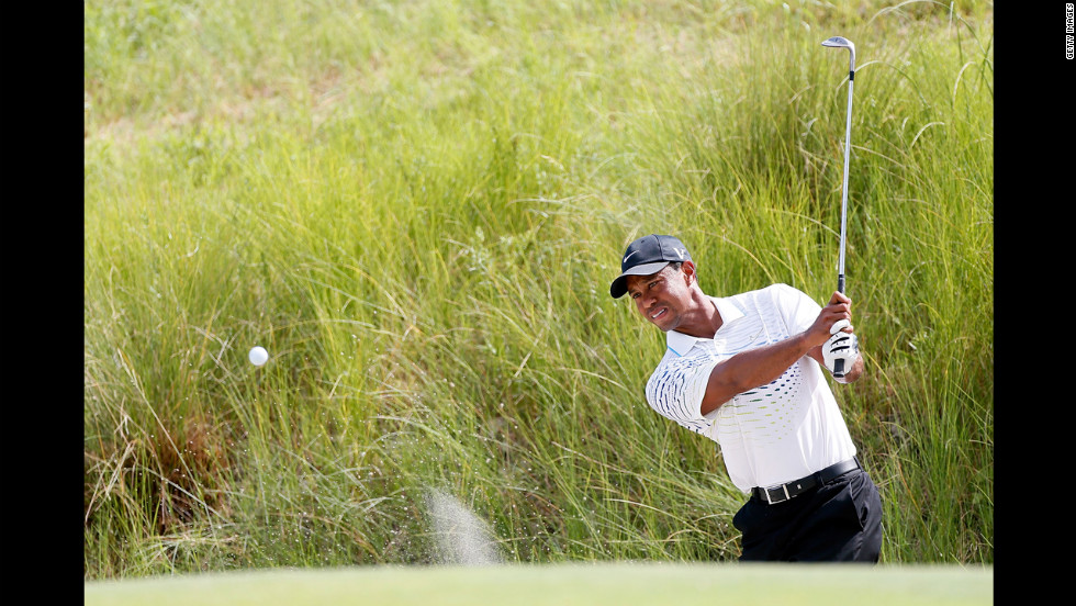 Tiger Woods of the United States hits out of the sand on the seventh hole.