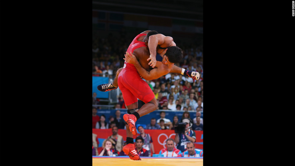 Livan Lopez Azcuy, in red, of Cuba grapples with Jabrayil Hasanov of Azerbaijan during the men's freestyle 66-kilogram wrestling bronze medal bout in London.